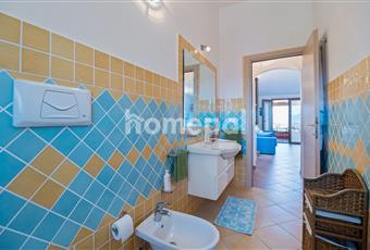 Bagno piastrellato spazioso con finestra, specchio a muro, lavandino con mobiletto e doccia.  Sardegna SS Valledoria