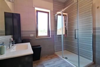 Ampio bagno luminoso. Mobile bagno sospeso, con lavabo e specchio. Sanitari sospesi. Ampio box doccia 80x140 in cristallo temperato. Il pavimento è costituito da listoni 15x90 in gres porcellanato effetto legno. Lazio LT Formia