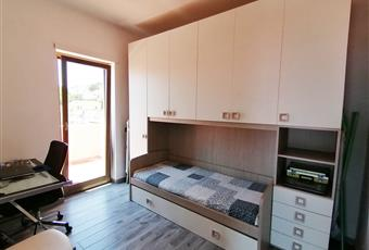 Camera da letto luminosa con vista mare. Il pavimento è costituito da listoni 15x90 in gres porcellanato effetto legno. Lazio LT Formia