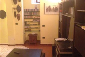 Piccolo salotto ricavato nell'open space dal quale è diviso da un muro in mattoni e vetro cemento.  Lazio RM Roma