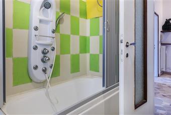 Bagno con pavimento piastrellato, fornito di lavatrice, scaldabagno nuovo e vasca con cabina cambiata da poco. Lombardia VA Varese