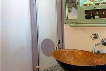 Stanza da bagno molto luminosa, con mobili in stile coloniale, lavabo di rame, vasca da bagno, doccia mosaicata con motivi in stile liberty Piemonte VB Premeno