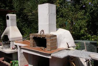 nella parte posteriore del giardino c'è un forno a legna e un barbecue in muratura. Sotto il forno è uno spazio per la sistemazione della legna.  Sardegna CA Capoterra