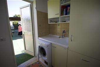 Il pavimento è piastrellato, la stanza è arredata con lavatrice, armadio, cesto portabiancheria, armadio per prodotti di pulizia, attrezzature da spiaggia, ombrellone scarpiera. Sardegna CA Capoterra