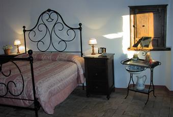 CAMERE DA LETTO DELLA CASA IN STILE RUSTICO: letti matrimoniali, arredamento con mobili d'epoca, soffitti con travi a vista e pavimento in cotto non trattato. La finestra di una camera si affaccia sul borgo sottostante, l'altra sulla via sotto il castello. Silenziose. Toscana GR Semproniano