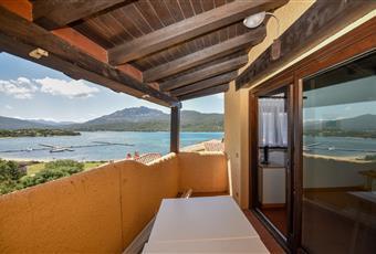 Terrazzo con tavolo sedie e sdraio, tende veneziane per il sole e una vista sulla laguna, spettacolare. Al tramonto il sole è dietro quelle colline e si ammira una luce magica! Sardegna OT Olbia