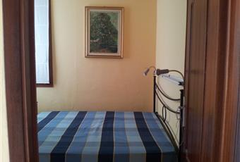 Una stanza matrimoniale con armadio e una stanzetta con letti a castello e terzo letto sotto il divano. Entrambe con finestra. Liguria IM Cervo