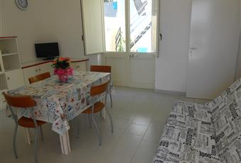 soggiorno molto luminoso con divano letto, camino, tavolo ,sedie e credenze Puglia LE Castrignano del capo
