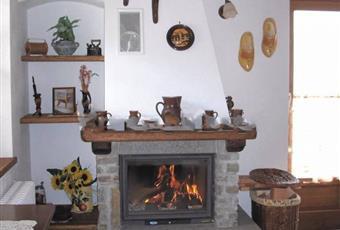 Il salone è con travi a vista, il salone è luminoso, il salone è con camino, il pavimento è piastrellato Valle d'Aosta AO Gressan